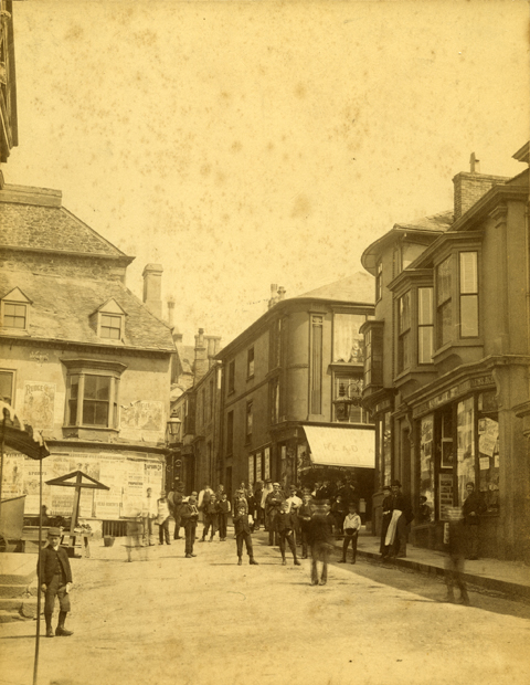 Market Place, Helston, taken from the Guildhall looking up towards Wendron Street, about 1880, by the local photographer Trevaskis.  Read and Roberts the tailors can be seen on the corner of Meneage Street and Wendron Street.  Bill hoardings can be seen on the building on the corner of Market Place and Wendron Street which would soon be demolished and become the site of the new Cornish Bank.  In 2016, this building is now Lloyds Bank.