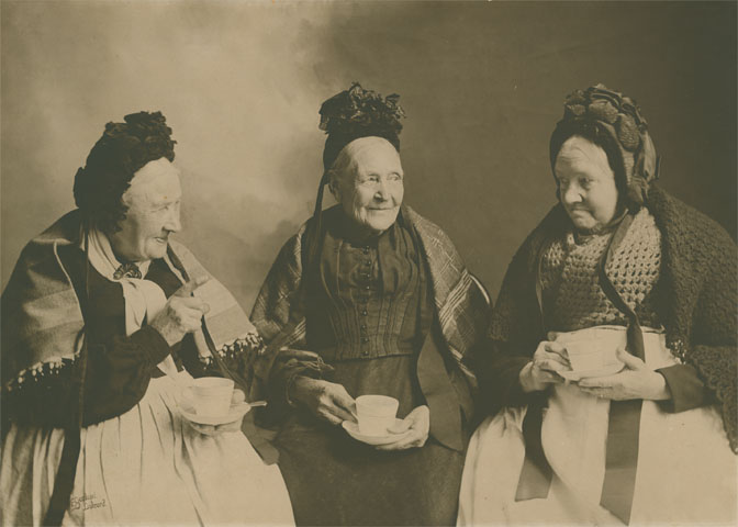 Three elderly Cornish ladies drinking tea, about 1910. The ladies are believed to be members of the Perry family of Helston.  Photograph by E Garland, Liskeard.