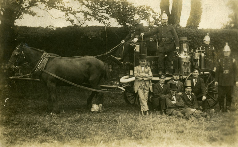 Photographic postcard of the Helston Borough horse drawn steam fire engine by A H Hawke of Helston, about 1910.  Five firemen in uniform are standing on and beside the fire engine.  Six men, five of whom are wearing top hats, are in front of the fire engine.