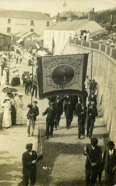 Photographic postcard of the Porthlevan Wesleyan Sunday School procession in the St Peter's Tide Parade, Porthleven, postmarked 30th July 1908.  Named after St Peter, the patron saint of fishing, local churches came together on this day to march through the village and ended with a treat of tea and saffron buns.  The parade is passing under Bay View Terrace.  The men are carrying the Porthleven Wesleyan Sunday School Banner and two members of the clergy can be seen walking underneath the banner, followed by the band and congregation.  There are a number of onlookers and all are in Edwardian dress.  The postcard is addressed to