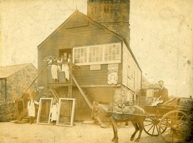 Nicholas carpenter's/builder's/undertaker's shop in Breage, about 1870, by S & J Govier of Breage.  The photograh shows the employees standing outside the works holding up windows and other employees standing up the stairs.  In the foreground is a man sitting on a horse and cart.