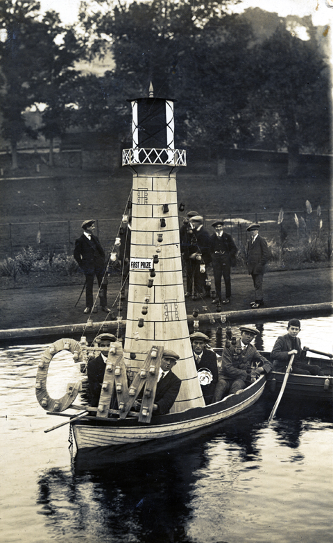 Photographic postcard of a carnival float exhibit on Coronation Lake, Helston, about 1913.  The lighthouse themed float won first prize at the Carnival.  Photograph by A H Hawke of Helston.