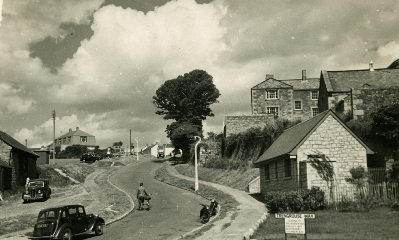 Trengrouse Way, Helston, about 1950.  A row of 5 cottages in Meneage Street were demolished in 1946 to provide access for this new road and Trengrouse Way was built in 1947.  The car parked by the sheds in the far left of the photograph is believed to have been owned by Harry Ferris.  He used the sheds to store stock for the family shop, E Ferris, a greengrocers and general store, at 70 Meneage Street.  The car parked on the road to the bottom left bears the registration number ERL 59.  A number of cars are parked in Trengrouse Way car park which opened in May 1948.  Some of the new prefabricated Cornish unit houses in Trevenen Road can be seen above the car park.  Meneage Hospital, the former workhouse, is on the right hand side.  The building has since been converted into residential accommodation.  The new electric street lighting seen in this image was introduced to Helston shortly before the photograph was taken.  Photograph by A H Hawke of Helston.