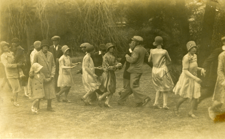 Photographic postcard of the Helston Flora Dance by A H Hawke of Helston, 1930. The dancers are dancing in a garden with overhanging trees. The gentlemen are wearing flat caps and suits, not morning suits and top hats, so presumably this is an image of the morning or evening dance. The ladies are in knee length dresses with cloche hats. Two lady onlookers are walking alongside the dancers with their smartly dressed children.  Part of the Jack Stephens Collection of local photographs.