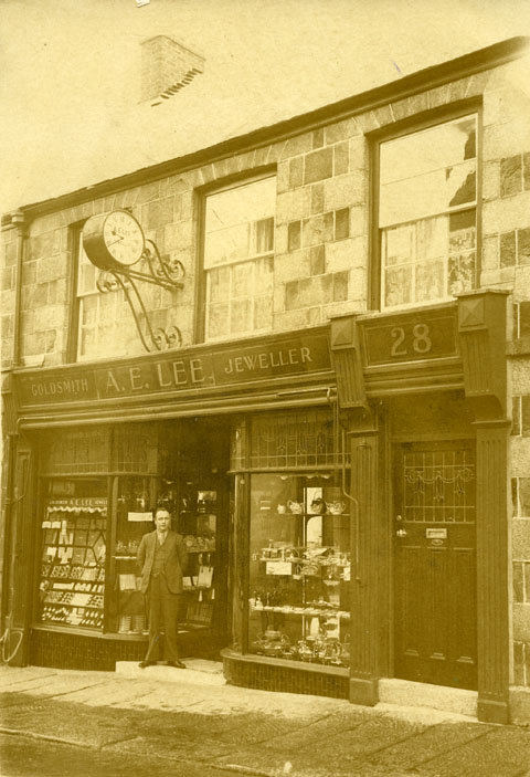 Arthur Evely Lee outside his Jewellers' shop at 28 Meneage Street, Helston, about 1928.  Arthur was born at Illogan in 1901 and first came to Helston in 1913.  He commenced his apprenticeship as a jeweller and watchmaker with George Beringer at the age of 14.  In 1922 he set up his own business at 9 Church Street and moved his premises to 28 Meneage Street in 1928.  He continued in business in Meneage Street until his retirement in 1959.  Arthur Evely Lee was first elected to the Town Council in 1957, became Mayor in 1962 to 1964 and was the last Member to be elected Alderman in 1972.  He was made Freeman in 1985 and died in 1993.  The clock seen above the shop was made by George Beringer and was originally above Beringer's premises at 18 Meneage Street.  Arthur purchased the clock for his own shop following George Beringer's death and converted it to motive power.  The clock is now in daily use in Helston Museum following it's conversion to electricity by Helston Town Council in 2000.